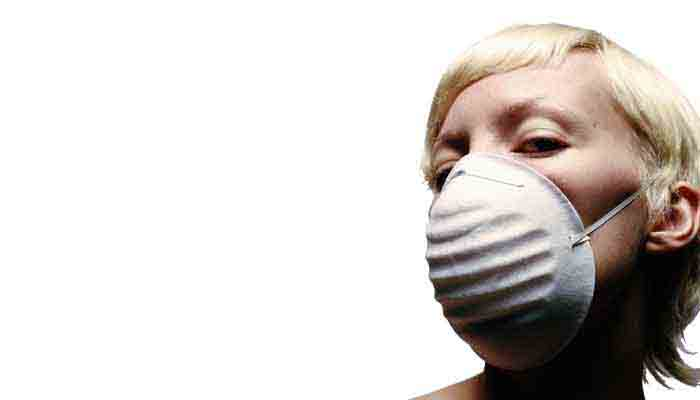 Close-up of young woman wearing a builder's dust mask